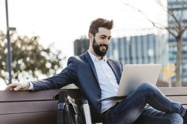 Businessman sitting on bench outside office building using laptop - JRFF01541