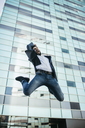 Businessman jumping outside office building - JRFF01547