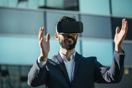 Businessman using virtual reality glasses outside office building - JRFF01550