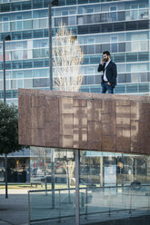 Businessman on cell phone outside office building - JRFF01556