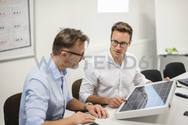 Two businessmen examining solar panel on desk in office - DIGF03292