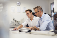 Two businessmen discussing plan on desk in office - DIGF03298