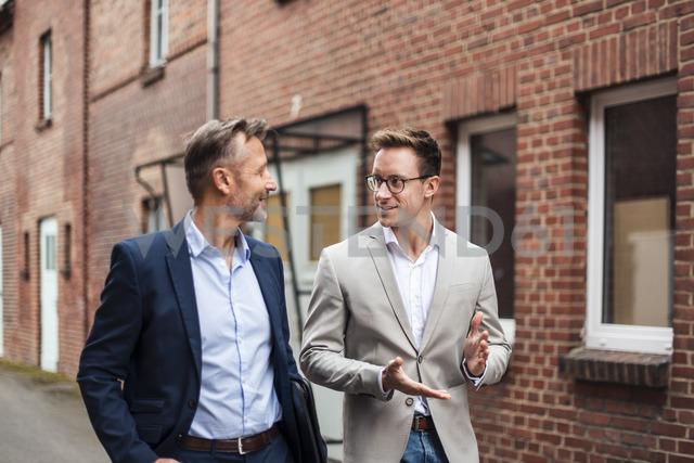 Two businessmen talking at brick building - DIGF03304