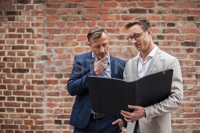 Two businessmen sharing folder at brick wall - DIGF03307