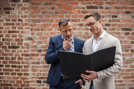 Two businessmen sharing folder at brick wall - DIGF03307