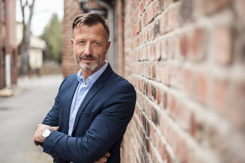 Portrait of confident mature businessman at brick wall - DIGF03310