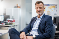 Portrait of confident mature businessman sitting at desk in office - DIGF03313