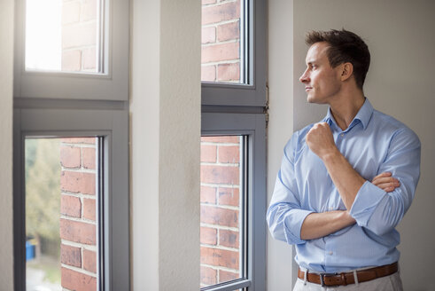 Young businessman looking out of window - DIGF03322