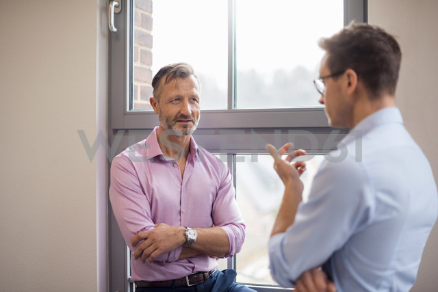 Two businessmen talking at the window - DIGF03325