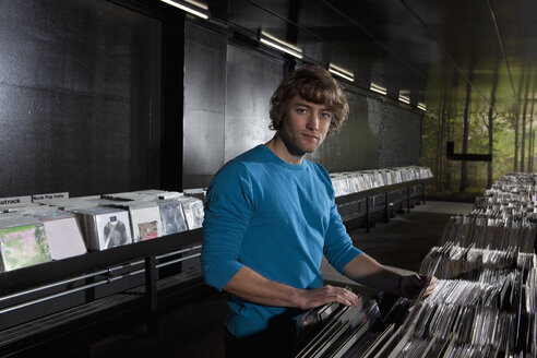 A young man in a record shop, looking at camera - FSIF00366