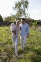 A man and a woman holding a baby walking in back of their country house - FSIF00441