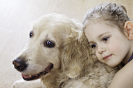 Close-up of a young girl hugging a dog - FSIF00459