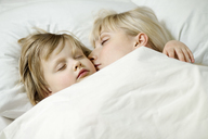 A mother and her young daughter sleeping a bed side by side - FSIF00468