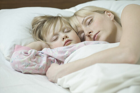 A mother and her young daughter sleeping a bed side by side - FSIF00471