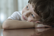 A young boy resting his head on his clasped hands, looking up and away - FSIF00474