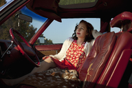 A pretty rockabilly woman sitting in the front seat of a vintage car - FSIF00486