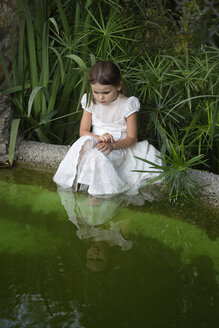 A young girl looking curiously into pond water - FSIF00519