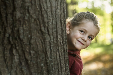 A young smiling girl peeking from behind a tree trunk - FSIF00522