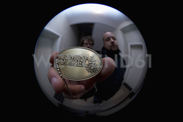 Two detectives showing a crime police (German: Kriminal Polizei) badge to a peephole - FSIF00549