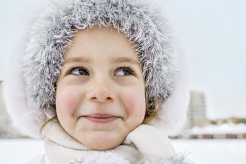 A mischievously smiling young girl wearing a fur hat outdoors in winter - FSIF00603
