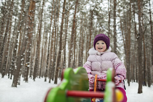 A young cheerful girl on a piece of playground equipment in winter - FSIF00609