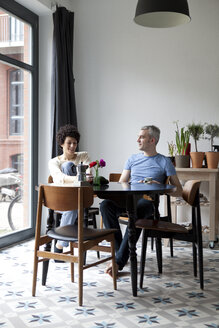 A cheerful hip mixed age couple enjoying breakfast together in their dining room - FSIF00627