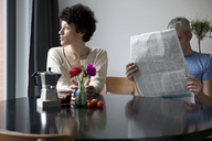 A serious woman looking out a window while her boyfriend hides behind a newspaper - FSIF00630