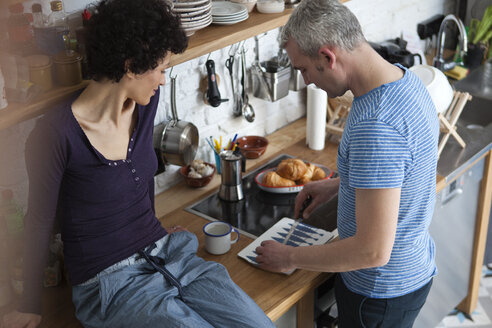 A smiling mixed age couple preparing food in their kitchen - FSIF00633