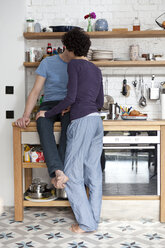 A mixed age couple kissing in their kitchen - FSIF00636