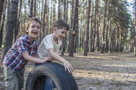 Two young boys pushing a tire in a wooded area - FSIF00693