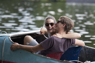 Young couple riding paddle boat, laughing - FSIF00708