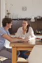 Young couple sitting at dining table in kitchen - FSIF00714