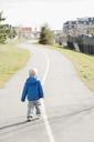 Full length rear view of baby boy walking on road - FSIF00810