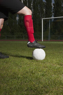 Low section of soccer player with foot on ball in front of goal post - FSIF00900