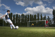 Full length of young soccer player kicking ball towards goal post - FSIF00903