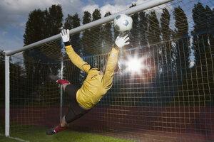 Full length of soccer goalkeeper diving to block ball - FSIF00906