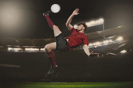Full length of soccer player kicking ball on field - FSIF00909