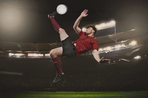 Full length of soccer player kicking ball on field - FSIF00909