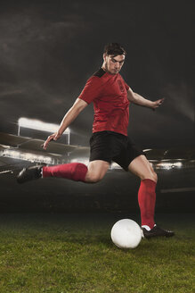 Full length of young soccer player kicking ball on field - FSIF00915
