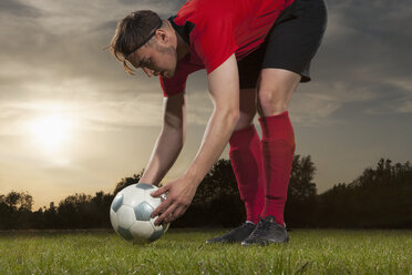 Full length of young soccer player positioning ball on field - FSIF00918
