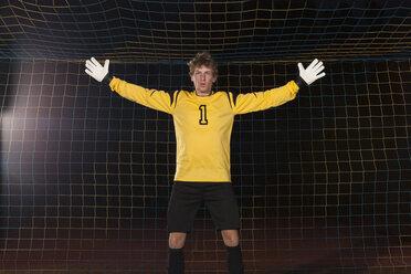 Portrait of confident goalie defending soccer net on field - FSIF00927