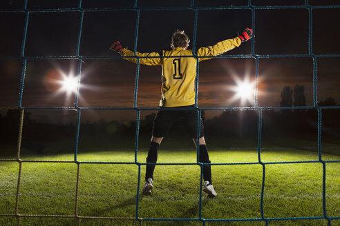 Full length rear view of goalie defending soccer net on field - FSIF00930