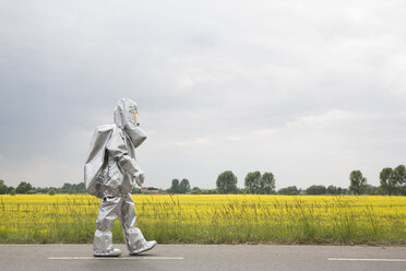A person in a radiation protective suit walking alongside an oilseed rape field - FSIF00933