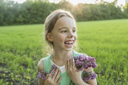Cheerful girl holding purple flowers on field - FSIF00936