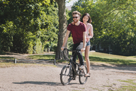 Full length of young couple riding bicycle at park - FSIF00963