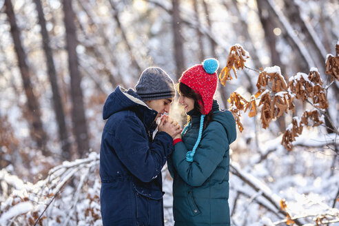 Side view of romantic young couple holding hands during winter - FSIF00990