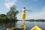 Rear view of boy jumping from canoe in lake - FSIF00999