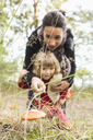 Mother showing mushroom to daughter on field - FSIF01005
