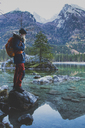 Side view of female hiker standing on rock at Lake Hintersee against mountains - FSIF01023