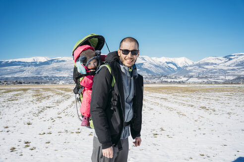 Spain, Puigcerda, father with baby girl in a kid carrier backpack during a hike at winter - GEMF01880